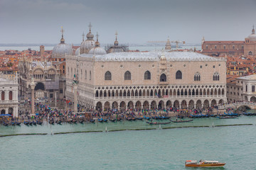 Aerial view of people and gondolas in front of Palazzo Ducale during high water, Venice, Italy