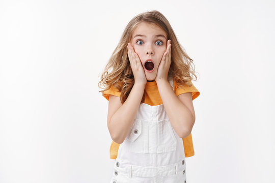 Scared and shocked caucasian blond little girl gasping, grab face amazed, stare camera astonished, drop jaw speechless observe shook event, react ambushed, frightened see spider, white background