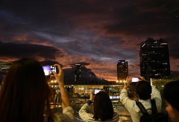 People take photos during sunset near Osaka Station, as typhoon 'Hagibis' approaches Japan