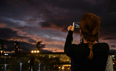 A woman takes a picture during sunset near Osaka Station, as typhoon 'Hagibis' approaches Japan