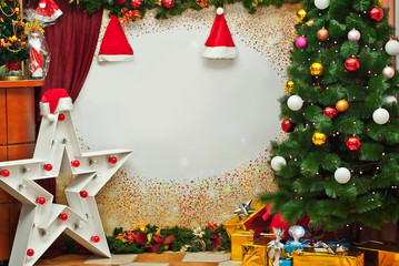 Christmas gifts near the Christmas tree. Holiday photo zone with decorations and decor. Part of the room is hung with Santa Claus garlands and hats. Free space for text on paper background.
