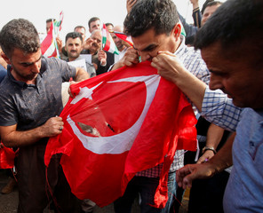 Iraqi Kurds tear the Turkish flag during a demonstration outside the United Nations building, against Turkey's incursion in Syria, in Erbil