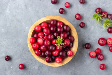 Fresh red cranberry in wooden bowl. Autumn harvest of wild berries. Above view.