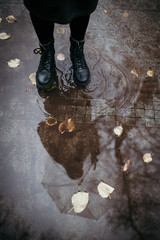 Girl in a coat, black shoes and with an umbrella. Autumn weather in the city, rain, reflection on the pavement. Drops of rain, fallen leaves.