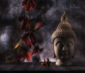 Buddha head statue and incense on a background red leaves. Buddhism and meditation concept