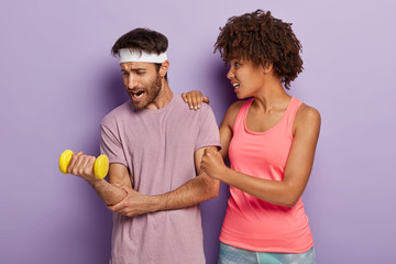 Caring supportive wife with Afro hairstyle, keeps hand on husbands shoulder, looks how he lifts heavy dumbbell, works on muscles. Fit sportsman demonstrates endurance and motivation to sport.