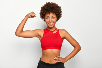 Horizontal shot of positive dark skinned woman shows biceps, demonstrates strong hand, has slim figure, wears sport bra, smiles pleasantly, isolated over white background. People and strength