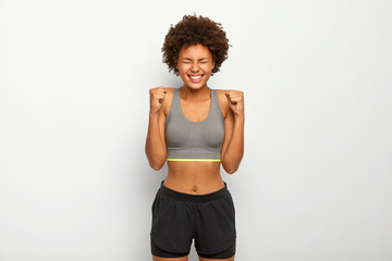Energized sporty woman rejoices winning, raises clenched fists, smiles broadly, wears sport bra , smiles broadly, isolated over white background, awaits for something. People, triumph, success concept
