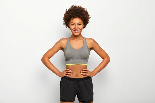 Photo of optimistic dark skinned sporty woman keeps hands on waist, smiles happily, dressed in sport bra and black shorts, isolated over white background, has fitтess training with instructor