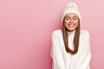 Horizontal shot of pretty young female with dark hair, keeps eyes shut, imagines pleasant moment, smiles pleasantly, shows white perfect teeth, enjoys comfort in new bought sweater, warm hat