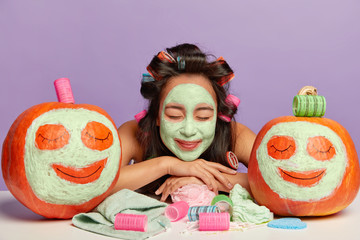 Satisfied brunette Korean woman leans at table with beauty products, applies clay nutrient facial mask and hair curlers, poses between comic pumpkins with applied cream, prepares for date. Face care