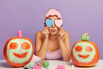 Image of young female cares about skin, covers both eyes with two heart shaped sponges, wears soft shower cap, has beauty treatments, applies clay facial mask on pumpkins, prepares for Halloween