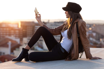 Pretty young woman taking a selfie with mobile phone while sitting on the rooftop.