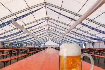 Fertiges und noch leeres Festzelt für das Oktoberfest mit, auf einem Holztisch steht ein Glas Bier
