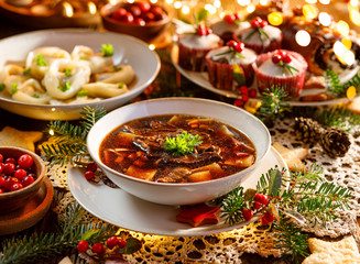 Christmas mushroom soup, a traditional vegetarian  mushroom soup made with dried forest mushrooms in a ceramik plate on a festive table. Polish Christmas dinner