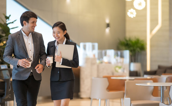 Asian business people  walking in office building. Young businessman and businesswoman talking when walking.