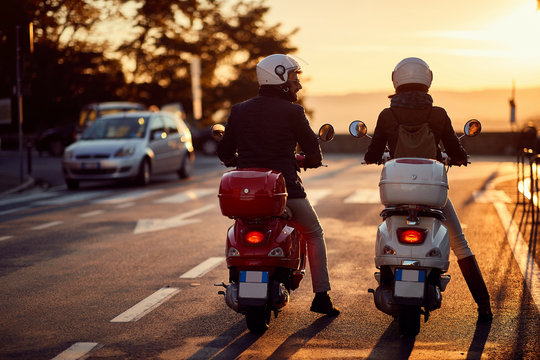 Couple riding motor scooter on road at sunset.