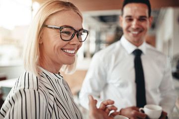 Smiling businesswoman talking with colleagues over coffee in an