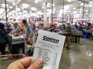 A hand holding Costco receipt