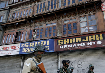 Kashmiri man looks out from a window as Indian security forces stand at the site of a grenade attack in Srinagar