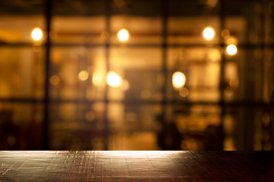 top of wood table with blur orange light of pub in bar in the dark night background