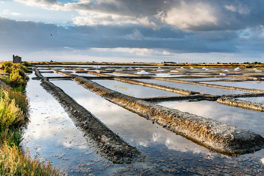 Salt marshes on the island of Noirmoutier in France..The sun rises on ponds, basins and .salt piles