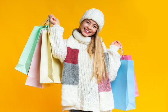 Positive young woman in winter hat holding colorful shopping bags