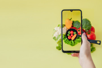 Girl taking picture of vegetarian food on table with her smartphone. Vegan and healthy concept.