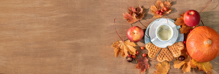 Autumn, fall leaves, a hot steaming cup of coffee, pumpkin and a warm sweater on a wooden table background. Panoramic image