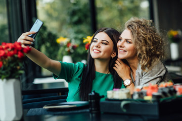 Pretty blonde and brunette girl taking a picture by the cell phone with sushi plate on table. Selfie time.