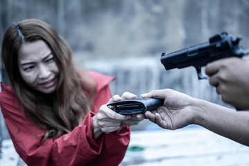 A man attacking holding gun for robbery to young woman. Crime and robbery concept. violence.