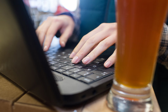 woman drinking beer while working with laptop