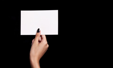 hand holding white card on black background - copyspace