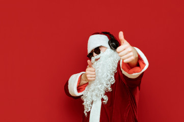Cheerful Santa Claus in sunglasses and headphones poses on red background, looks at camera and shows thumbs up. Like it, he shows the gesture. Christmas like. Copyspace