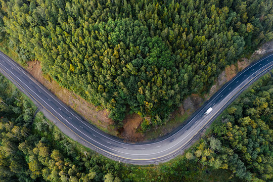 Top down aerial view of mountain road curve among green forest trees. Small cargo truck on the highway. P-258 road on the shore of Baikal Lake near Baikalsk, Buryatia, Russia