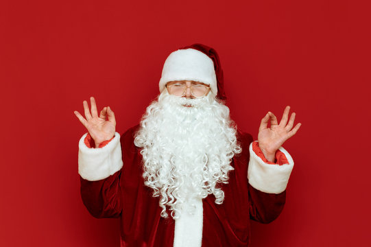 Santa Claus meditates on a red background, stands on a red background with his eyes closed. Santa is practicing yoga. Christmas yoga with Santa. New Year concept.