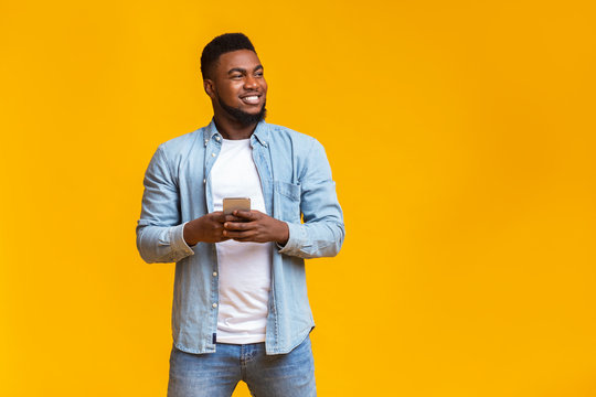 Handsome guy holding smartphone and looking aside at copy space