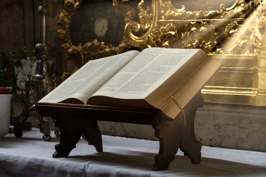Open bible illuminated by sunbeams on an altar