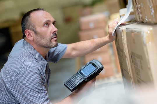 worker with portable barcode scanner in warehouse