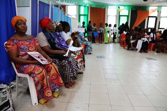 Women sit as they wait for screenings during the breast cancer prevention campaign in Abidjan, Ivory Coast