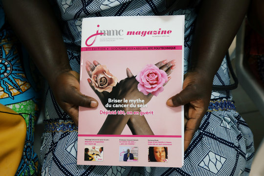 A woman holds a breast cancer awareness journal as she waits for a screening during the breast cancer prevention campaign in Abidjan, Ivory Coast