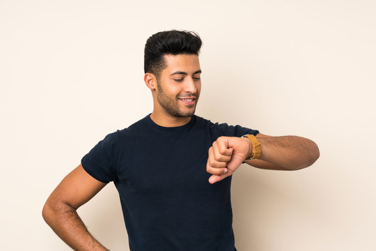 Young handsome man over isolated background looking the wrist watch