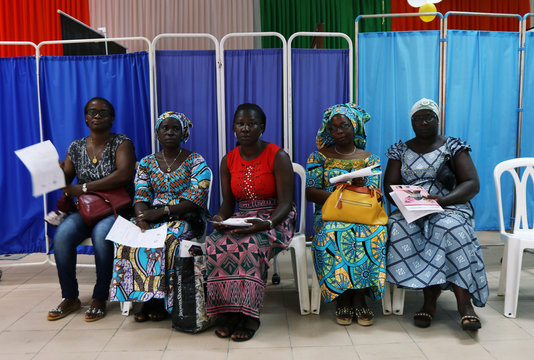 Women sit as they prepare for screenings during the breast cancer prevention campaign in Abidjan, Ivory Coast