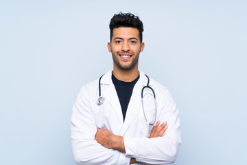 Young doctor man over isolated blue wall smiling a lot