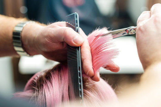 Close up of hairdresser's hands are cutting pink tips while getting rid of split ends at hair salon. Beauty hairstyle concept.