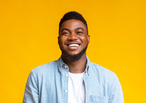 Portrait of young laughing african american guy over yellow background