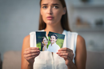 Sad Girl Ripping Photo With Ex-Husband Indoor
