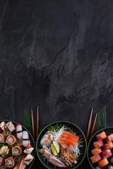 Foto op Plexiglas Sushi bar Assorted sushi set on dark slate background. Sushi maki roll with salmon, scallop, eel and prawn sashimi served with daikon radish. Copy space for text. Restaurant menu. Traditional japanese food.