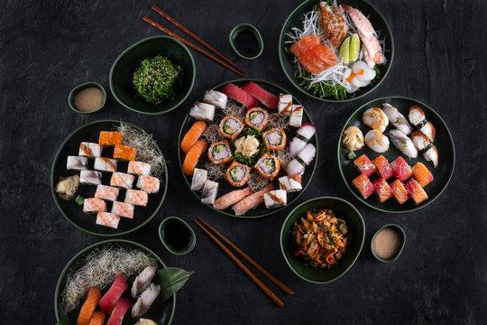 Assorted sushi set served on dark stone slate background. Top view of wakame salad, seafood,various maki rolls, sashimi and nigiri with caviar, prawn, scallop, octopus, salmon, eel, mackerel and tuna