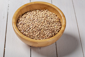 Uncooked green lentils on wooden black table